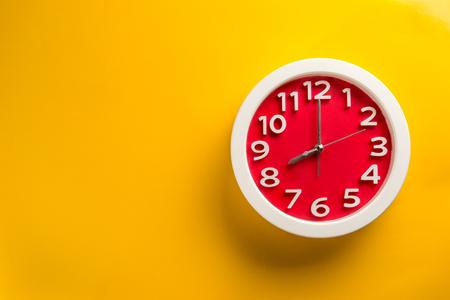 Foto de Red clock on yellow background .Make on color background concept - Imagen libre de derechos