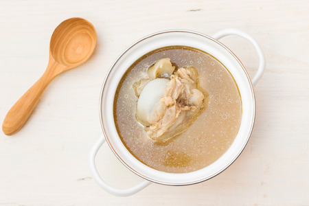 Photo for Bowl of pork bone soup with herbs on wood table - Royalty Free Image