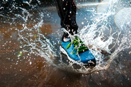 Single runner running in rain and making splash in puddle