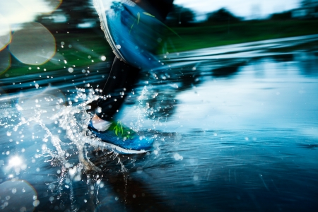 Photo pour Single runner running in rain and making splash in puddle - image libre de droit
