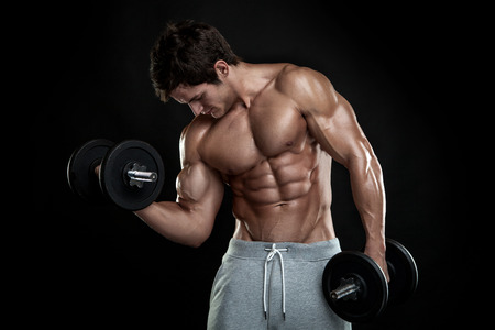 Foto de Muscular bodybuilder guy doing exercises with dumbbells over black background - Imagen libre de derechos