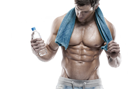 Foto de Strong Athletic Man Fitness Model Torso showing six pack abs. holding bottle of water and towel - Imagen libre de derechos