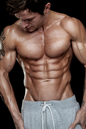 Photo for Strong Athletic Man Fitness Model Torso showing six pack abs. isolated on black background - Royalty Free Image