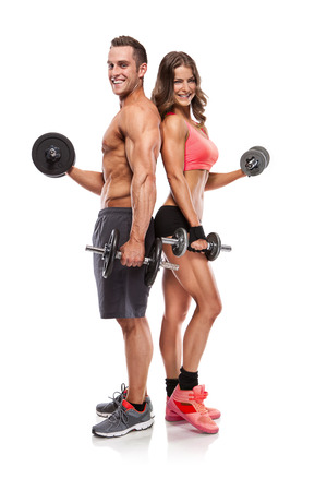 Foto de beautiful fitness young sporty couple with dumbbell isolated over white background - Imagen libre de derechos