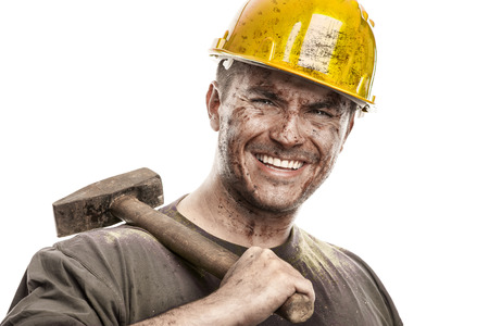 Foto de Young dirty Worker Man With Hard Hat helmet  holding a hammer isolated on White Background - Imagen libre de derechos