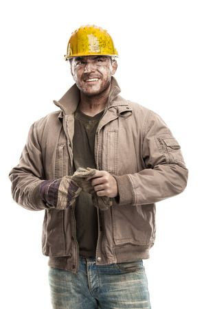 Photo pour Young dirty Worker Man With Hard Hat helmet  holding a work gloves and smiling isolated on White Background - image libre de droit