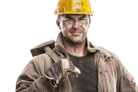 Photo pour Young dirty Worker Man With Hard Hat helmet  holding a hammer and smiling isolated on White Background - image libre de droit