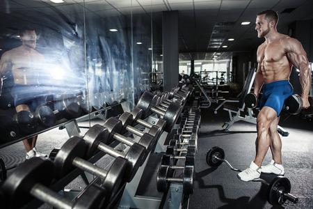 Foto de Muscular bodybuilder guy doing exercises with dumbbell in gym - Imagen libre de derechos