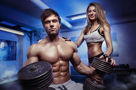 Foto de beautiful young sporty sexy couple showing muscle and workout in gym - Imagen libre de derechos