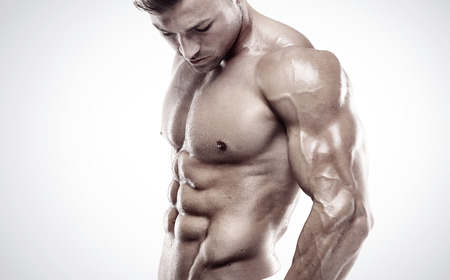 Photo pour Muscular bodybuilder guy standing and posing triceps muscle - image libre de droit
