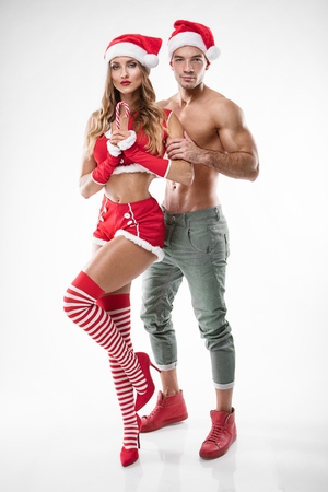 Photo for beautiful sexy couple in santa claus clothes over white background - Royalty Free Image