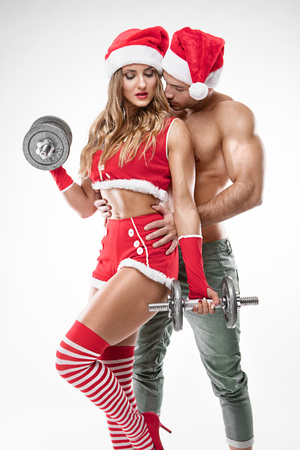 Photo for beautiful sexy couple in santa claus clothes doing workout with dumbbell over white background - Royalty Free Image