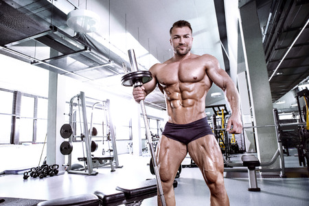 Photo for Muscular bodybuilder guy doing exercises with dumbbell in gym - Royalty Free Image