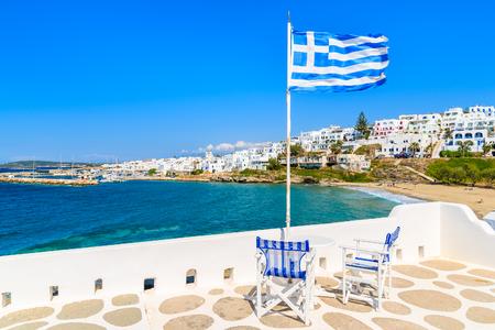 Foto de Chairs with table on a terrace with Greek flag in Naoussa village, Paros island, Greece - Imagen libre de derechos