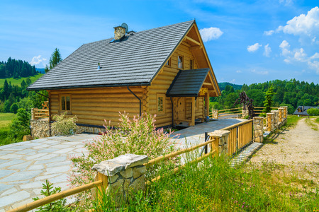 Photo pour Traditional wooden mountain house on green field in summer, Szczawnica, Beskid Mountains, Poland - image libre de droit