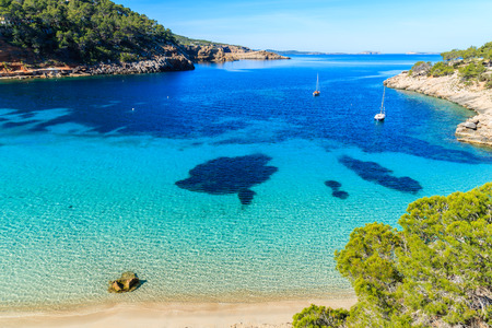 Foto per View of beautiful beach in Cala Salada famous for its azure crystal clear sea water, Ibiza island, Spain - Immagine Royalty Free