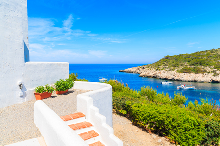 Photo for Steps to traditional white house and view of fishing boats on sea in Cala Portinatx bay, Ibiza island, Spain - Royalty Free Image