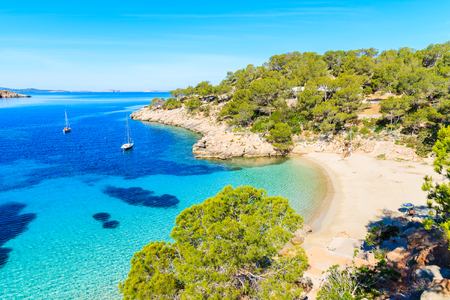 Foto per View of beautiful beach in Cala Salada bay famous for its azure crystal clear sea water, Ibiza island, Spain - Immagine Royalty Free