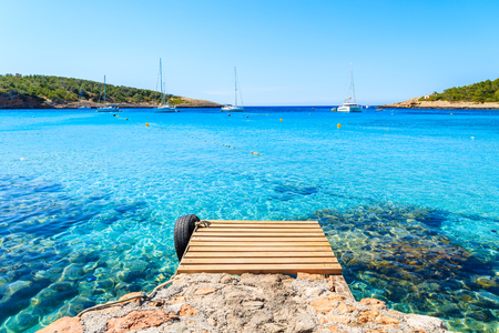 Photo pour Wooden jetty and view of azure blue sea with sailing boats in distance, Cala Portinatx bay, Ibiza island, Spain - image libre de droit