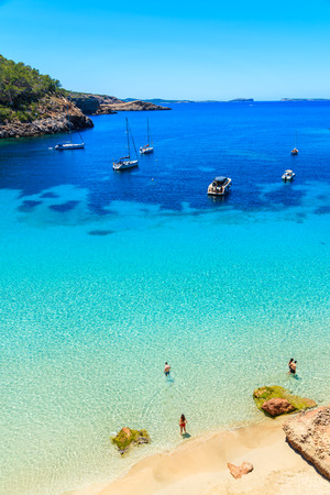 Photo pour Unidentified two young couples on beautiful beach in Cala Salada bay famous for its azure crystal clear sea water, Ibiza island, Spain - image libre de droit