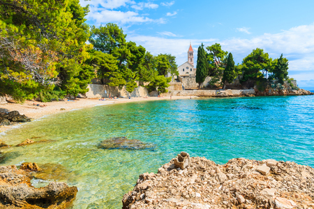 Foto de Beach with emerald green sea water and view of Dominican monastery in distance, Bol town, Brac island, Croatia - Imagen libre de derechos