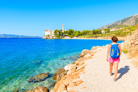 Foto de Young woman tourist walking on coastal path along sea to Dominican monastery in Bol town, Brac island, Croatia - Imagen libre de derechos
