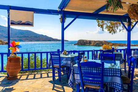 Foto de Terrace with tables in traditional Greek tavern with sea view in Lefkos village on Karpathos island, Greece - Imagen libre de derechos