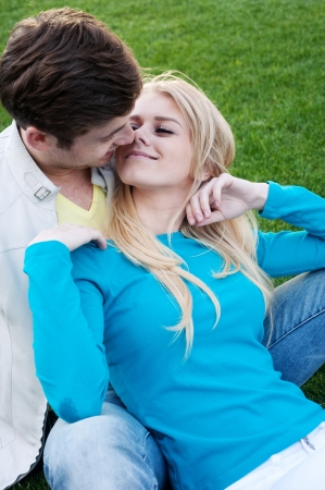 young happy couple in love sitting in grass