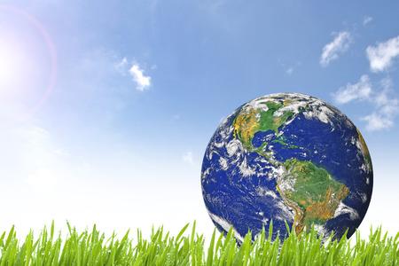 Foto de Planet Earth on beautiful green grass and sunny day with blue cloudy sky  - Imagen libre de derechos