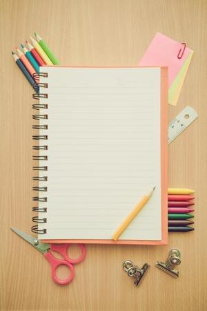 Foto de Top view of education and business supplies on wooden table with empty space notepad - Retro filter effect - Imagen libre de derechos