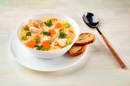 Foto de Chicken soup with noodles, bread, and copy space - Imagen libre de derechos