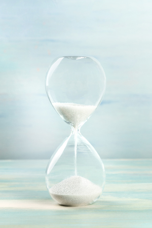 Foto de A side view of an hourglass with falling sand, on a teal background with copy space - Imagen libre de derechos