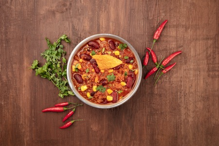 Foto de Chili con carne, traditional Mexican dish, shot from the top on a dark wooden background with ingredients and copy space - Imagen libre de derechos
