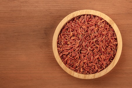 Foto de A photo of a long grain red rice, shot from above in a wooden bowl on a dark rustic background with copy space - Imagen libre de derechos