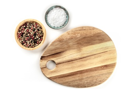 A photo of a cutting board with sea salt and pepper, shot from above on a white background with a place for text