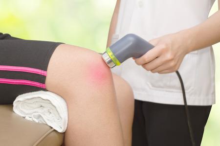 Foto de Physical therapist using ultrasound probe on woman patient 's knee for release pain - Imagen libre de derechos
