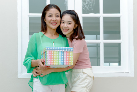 Photo for Joyful Asian mother and teenage girl holding gift box and smile,mother day - Royalty Free Image