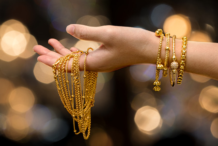 Foto de woman hand hold gold bracelet and necklace  jewelry - Imagen libre de derechos