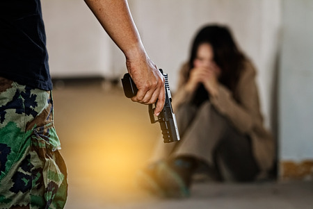 Foto de Woman kidnapped by criminals who threatening her by gun. - Imagen libre de derechos