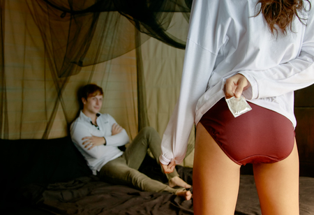 Foto de Back view of sexy woman holding a condom while her boyfriend is lying on bed - Imagen libre de derechos
