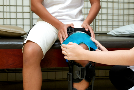 Photo for Physical therapist applying cold compress on patient knee to reduce pain - Royalty Free Image