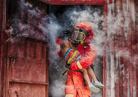 Foto de Emergency Fire Rescue training,Firefighters save the boy from burnt place - Imagen libre de derechos