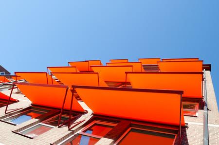 Foto de Windows at the flats with orange shade sail sun protection. - Imagen libre de derechos