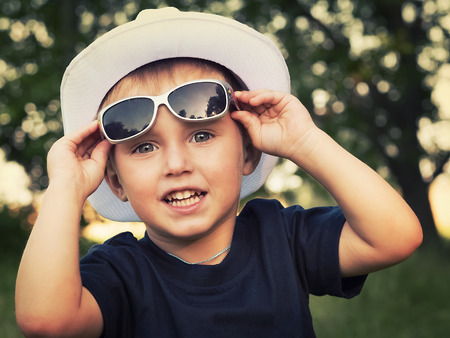 Photo pour Portrait of a cheerful little boy in sunglasses - image libre de droit