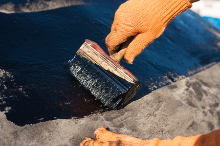 Photo for Roofer cover the concrete base, polymer modified bitumen waterproofing primer. A worker brushes cover concrete, bitumen-rubber primer. - Royalty Free Image