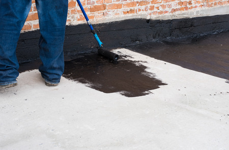 Photo pour Worker covered surface, bitumen primer for improving adhesion during surfacing,  rolled waterproofing, during the installation of isolation on industrial or household objects - image libre de droit