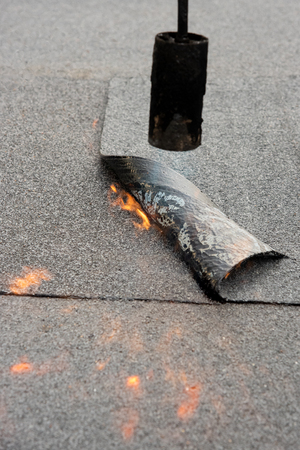 Photo for Preheating the edges of the roofing material. - Royalty Free Image