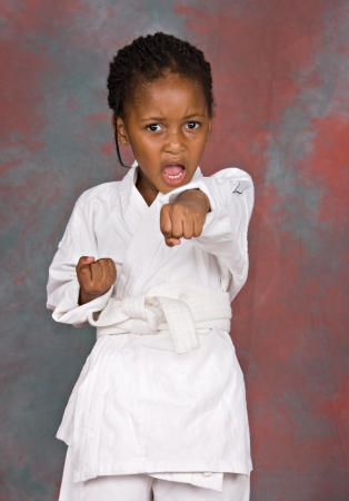 Small karate girl training , on colorful  background