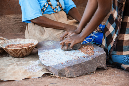 Photo pour African woman in the village grinding traditionally some seeds - image libre de droit