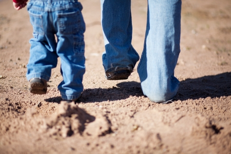 Photo for Father and son walking together in the sand - Royalty Free Image